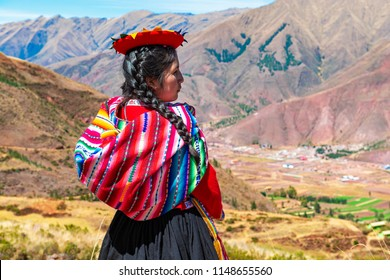 TIPON, PERU - JULY 24, 2018: Young Quechua indigenous woman with traditional clothing looking over the Sacred Valley of the Inca and Urubamba valley near the city of Cusco in the Andes mountain range.