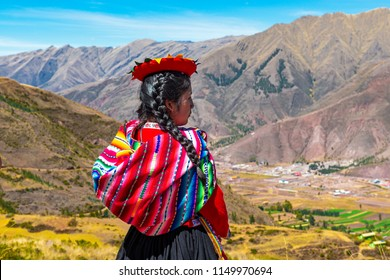 TIPON, PERU - JULY 24, 2018: Young indigenous Quechua woman in the Inca archaeological site of Tipon near Cusco city.