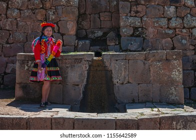 TIPON, PERU - JULY 24, 2018: Quechua indigenous girl in traditional clothing by a fountain in a Inca archaeological site near Cusco.