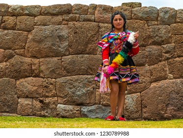 TIPON, PERU - OCTOBER 2, 2018: Young Quechua indigenous girl with traditional clothing and hair style in front of an ancient Inca wall in the archaeological ruins of Tipon near Cusco.