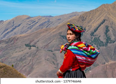 TIPON, PERU - SEPTEMBER 22, 2018: Portrait of an indigenous Quechua girl looking behind her with the Andes mountain range in the background near Cusco, Peru.