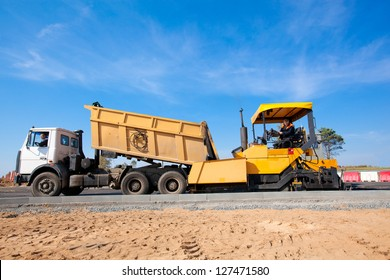 Tipper unloading fresh asphalt from body into tracked paver during road construction works