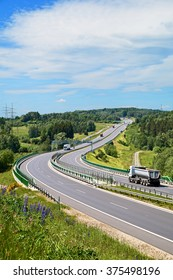 Tipping lory and trucks traveling on the asphalt highway with electronic toll gates in a wooded landscape. View from above. Sunny summer day.
