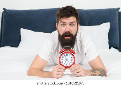 Tips for becoming an early riser. Problem with early morning awakening. Get up with alarm clock. Overslept again. Tips for waking up early. Man bearded hipster sleepy face in bed with alarm clock.
