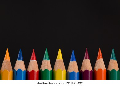 Tips of Colored pencils on black background. back to school. copy space