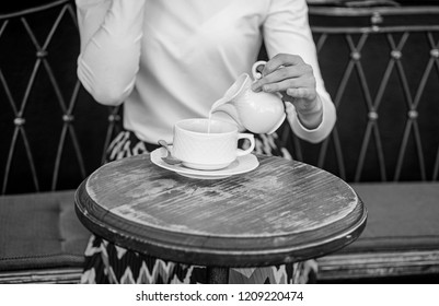 Tips for healthier coffee drinking. Hand female adding pouring milk to black coffee outdoors cafe terrace, close up. Mug americano or black coffee and jug with milk. With milk tastes better.