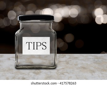Tips jar empty. Low wage issue. Bokeh background as though in a bar, restaurant.