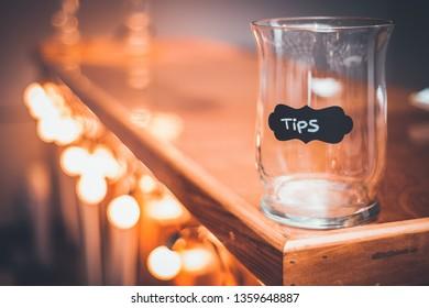 Tips Jar on a bar countertop. Bokeh lights along a bar counter with a tip Jar at the end. Gold Bokeh lights.