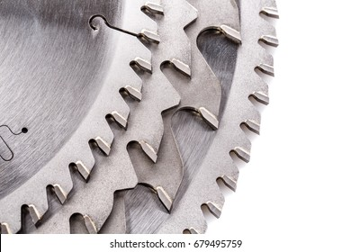 The tips of the teeth of a new ripping saw blade on a white background.
