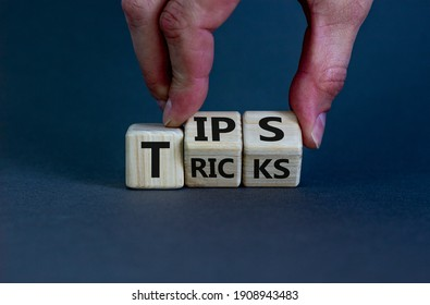 Tips and tricks symbol. Businessman turns cubes and changes the word 'tricks' to 'tips'. Beautiful grey background. Business, tips and tricks concept. Copy space.