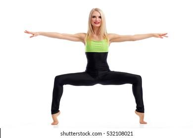 Tiptoe balance. Beautiful fit active woman smiling to the camera while doing squats balancing on her tiptoes with her arms spread to the sides isolated fitness strength squats concept