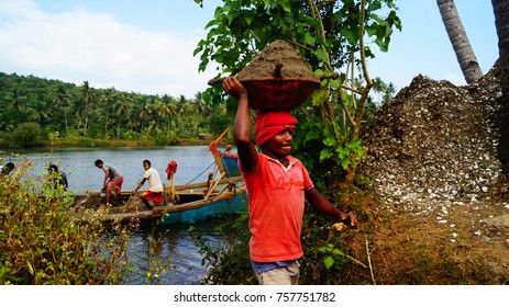 Tirakhol river, Goa/ India - November 5, 2017: Traditional Indian work. Indian people with a basket full of sand from Maharashtra. Business in India. Close up portrait of Indian man carrying a basket.