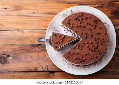 Tiramisu cake with chocolate decoration on a plate. Wooden background. Copy space. Top view.
