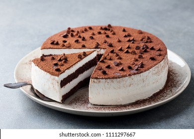 Tiramisu cake with chocolate decotaion on a plate. Grey background. Close up.