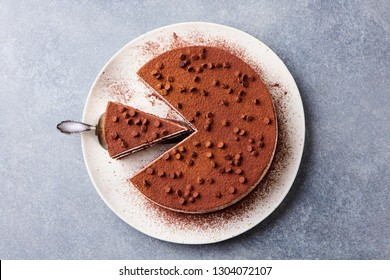 Tiramisu cake with chocolate decotaion on a plate. Grey stone background. Top view.