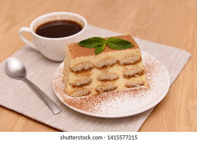 Tiramisu cake with coffee and fresh mint, on a plate on a light wooden background. Selective focus.
