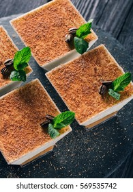 Tiramisu dessert in square Glasses on the Black Background