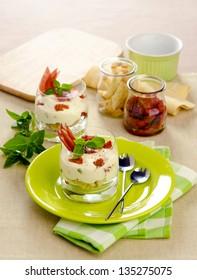 Tiramisu with dried tomatoes and ham in glass