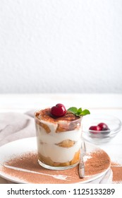 Tiramisu in a glass cup and ingredients on the wooden background