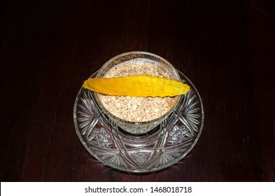 Tiramisu in a glass topping with ground nuts and garnish with dry mango slice