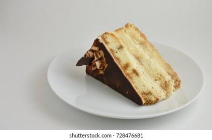 Tiramisu layered cake on white plate with chocolate powder, swirled icing, white background.