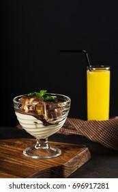 Tiramisu, traditional Italian dessert in glass on a wood plate and grey stone background. Orange juice on napkin.