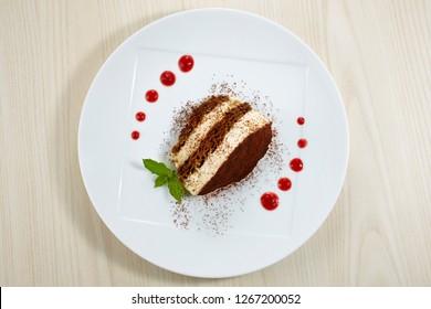 Tiramisu, traditional Italian dessert on a white plate.