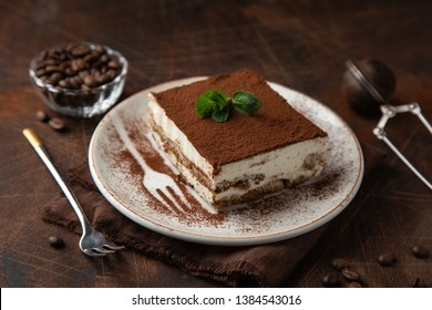 Tiramisu. Traditional italian dessert on white plate, wooden background. Selective focus