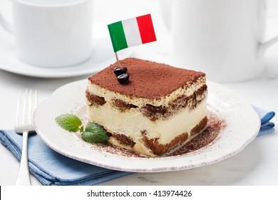 Tiramisu, traditional Italian dessert on a white plate with Italian flag