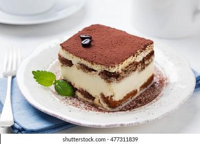Tiramisu, traditional Italian dessert on a white plate. Close up.