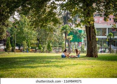 TIRANA, ALBANIA - AUGUST 10, 2018: Front view of two young woman sitting resting under a large tree in a city park in Tirana Albania August 10, 2018. Incidental people and buildings in the background.