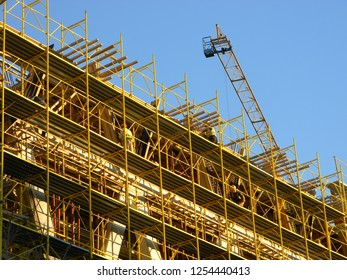 Tirana, Albania - December 5 2018: Construction workers standing on yellow scaffolding, working on a new building, with a crane jib in the background