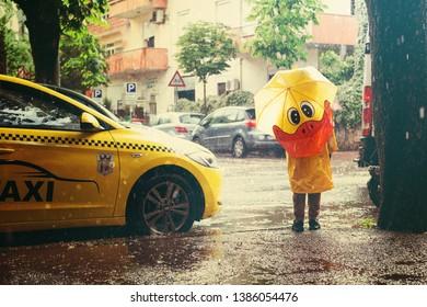 Tirana, Albania. May 2019: child with yellow umbrella under the shower rain. Child is wearing yellow raincoat and enjoying rainfall.