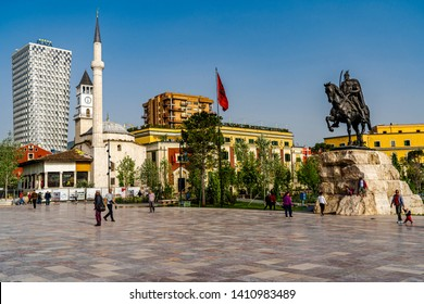 Tirana, Albania-4/24/2019: The history of Albania is shown in the photo with the statue of Skanderbeg, the Albanian flag, the minaret in this Muslim country, an Ottoman clocktower and modern hotel