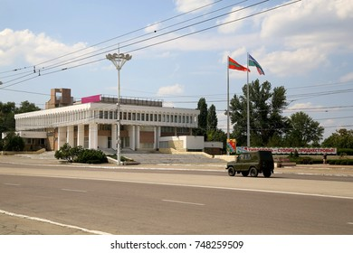 TIRASPOL, TRANSNISTRIA – CIRCA JULY 2017: Street in Tiraspol on July 2017. Street in Tiraspol. UAZ car is passing in front of Palace of Children and Youth Creativity.