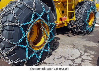 Tire chains for better traction in snow and ice travel on large commercial rubber tire of heavy equipment