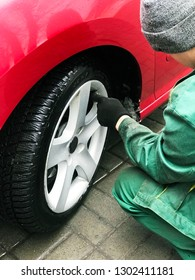 Tire fitter in green work clothes checks tire pressure. Preparing the car for a trip on the winter off-road. Maintenance.