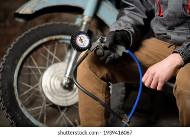 A tire fitting service worker is sitting with a car tyre inflation gun on a motorbike wheel background.