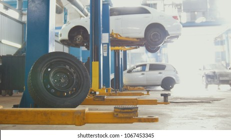 The tire in front of a service station with cars on the lift