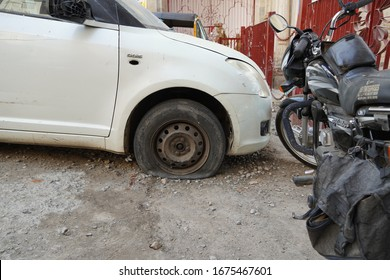 Tire leak, close up wheel of old white vintage car. Car wheel flat tire on the road. Deflated the tyre of an old car next to a motorcycle. - Udaipur India : February 2020