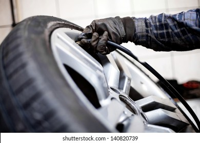 Tire pressure check. Closeup of mechanic inflating tyre with alloy wheel