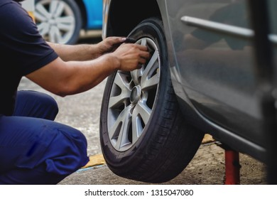 Tire Replacement concept. Mechanic Working his Job with Wheel in Garage. Car Maintenance and services