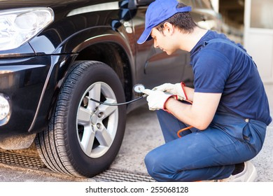 Tire specialist checking the pressure of a tire