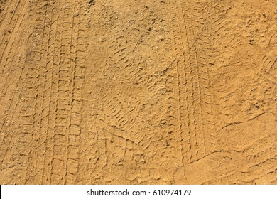Tire trace on country road with sand and soil background