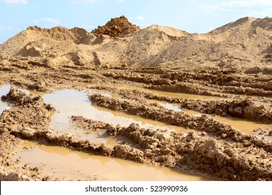 Tire track on the wet soil near the construction side. Construction dirt pile. Large hill of sandy soil with vehicle tire tracks on the surface. Blue sky and clouds background.