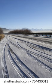 Tire tracks in fresh snow early in winter in a pull out on a highway in Southeast Alaska on the Chilkat River.