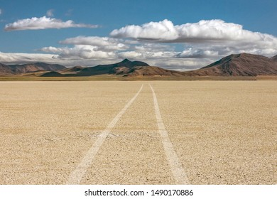 Tire tracks lead into distance across dry lake bed in remote desert landscape