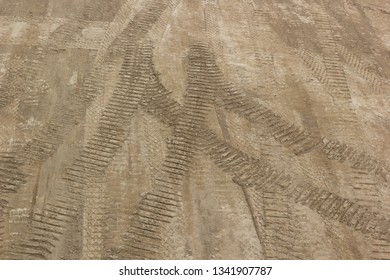 Tire tracks on a brown dirt road, textured imprints