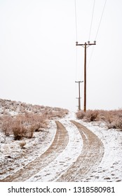 tire tracks in snow on desert dirt road lined with power poles and electric lines