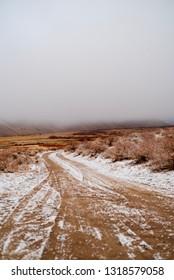 tire tracks in snow on dirt road in desert valley Sierra Nevadas, California, USA